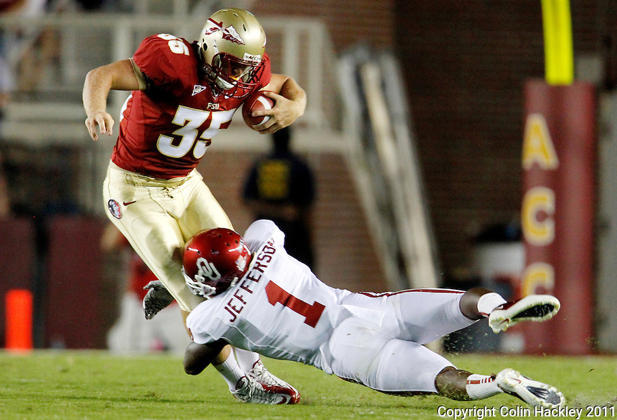 TALLAHASSEE, FL 9/17/11-FSU-OU091711 CH-Florida State's Nick O'Leary is tackled by Oklahoma's Tony Jefferson during first half action Saturday at Doak Campbell Stadium in Tallahassee. .COLIN HACKLEY PHOTO