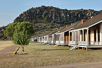 Shared lieutenants' living quarters, built 1882 in Officers' Row, at Fort Davis National Historic Site, a US army fort established 1854, in a canyon in the Davis Mountains in West Texas, USA. The lodgings were built for a captain but were soon designated a shared quarters. It is refur­bished for a bach­elor lieutenant in the north side and a married lieutenant in the south side. The fort was built to protect emigrants, mail coaches, and freight wagons on the trails through the State from Comanche and Apache Indians. After the Civil War, several African-American regiments were stationed here. By the 1880s, the fort consisted of one 100 buildings, housing over 400 soldiers. It was abandoned in 1891, but many buildings have been restored and the compound now operates as a historical site and museum. Picture by Manuel Cohen