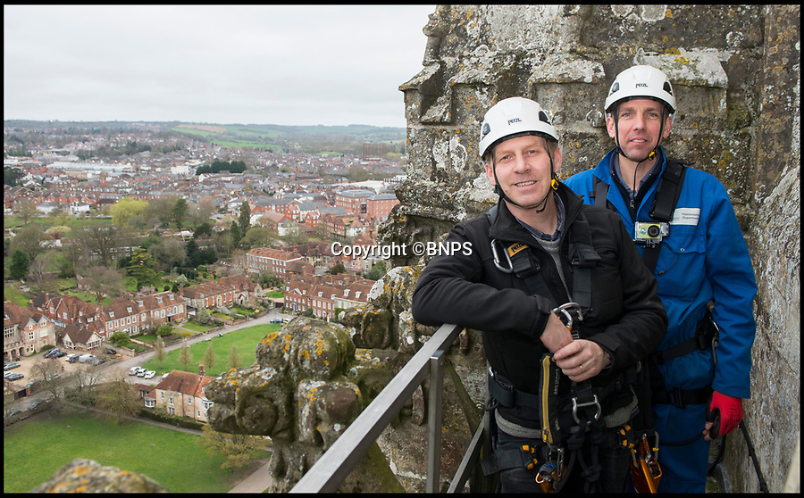 BNPS.co.uk (01202 558833)<br /> Pic: TomWren/BNPS<br /> <br /> Clerk of the Works, Gary Price (left) and Ecclesiastical carpenter Richard Pike take in the view at the bottom of the spire.<br /> <br /> How many men does it take to change a lightbulb... at the top of Britain's tallest spire.<br /> <br /> When your office is Salisbury Cathedral the simple task of changing a light bulb involves four men, a 404ft climb and takes three hours.<br /> <br /> Ecclesiastical carpenter Richard Pike needed a head for heights when he joined Gary Price, who is in charge of conservation, to make the daring ascent with two rope specialists to ensure their safety. <br /> <br /> Despite working at the cathedral for 27 years, it was the first time Richard has ever made the hair-raising climb.