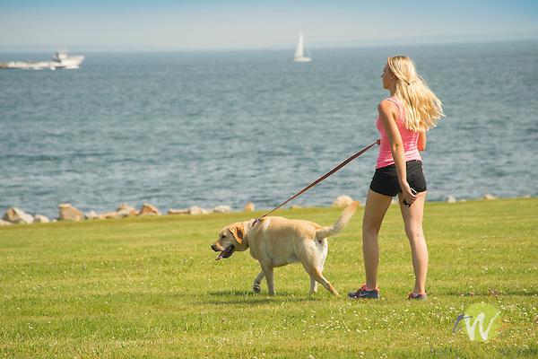 Harkness Memorial State Park. Woman walking Golden Labrador.