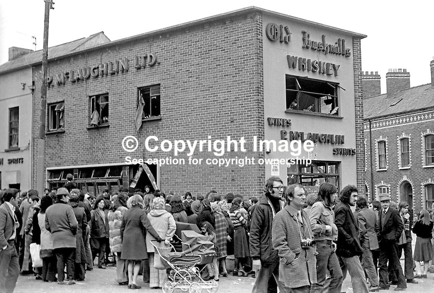 Hundreds of people outside McLaughlin's Bar, Antrim Road, Belfast, N Ireland, following an explosion in which 2 died and 15 were injured. The gas cylinder bomb was planted by the UVF. The incident occured whilst the bar was packed with customers watching the Grand National.  Later the same day a retaliation bombing took place at the Mountainview Tavern on the Loyalist Shankill Road in which 5 Protestants died. 5th April 1975. 197504050355a<br />