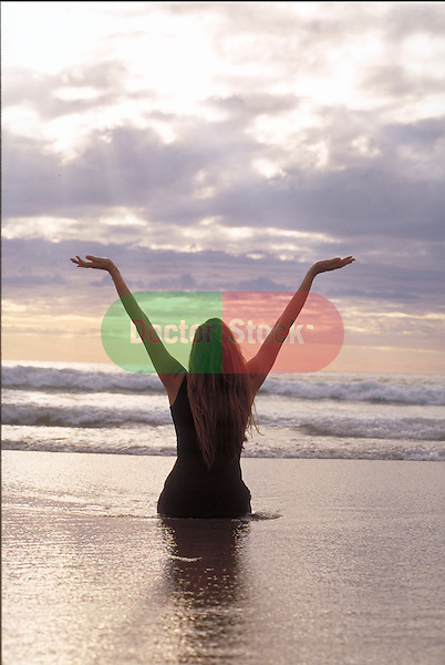 woman in water at beach with arms raised