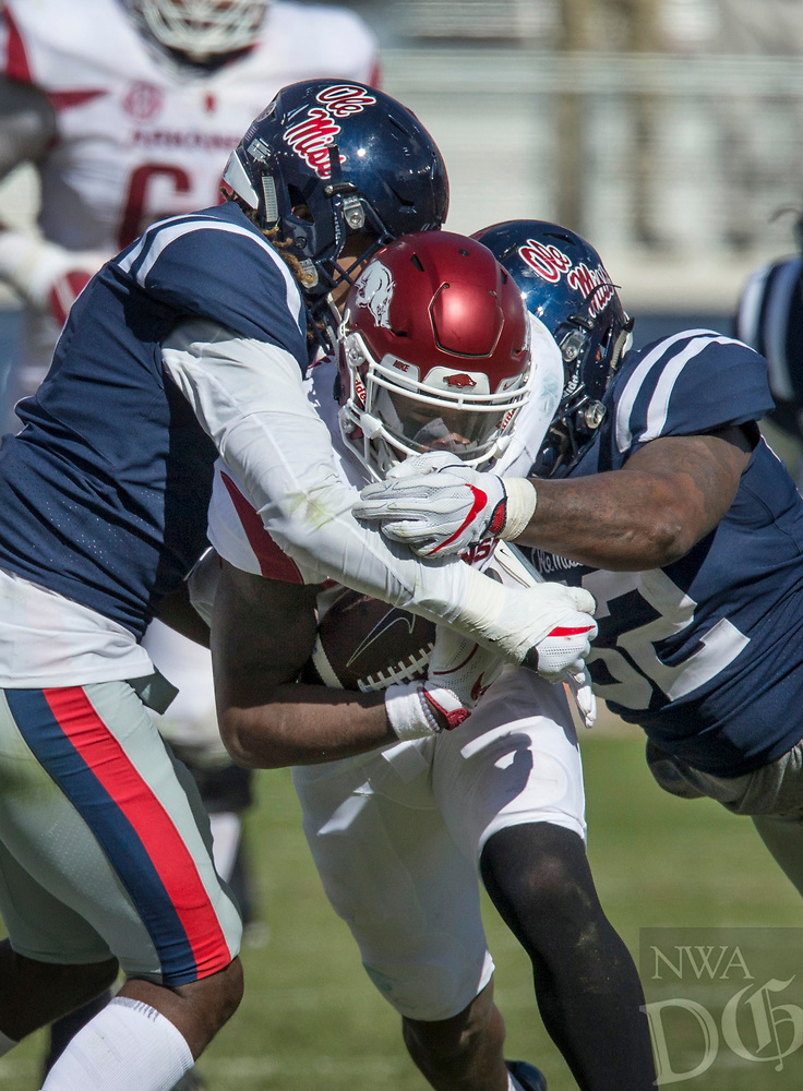 Hawgs Illustrated/BEN GOFF <br /> T.J. Hammonds, Arkansas running back, tries to split D.D. Bowie, Ole Miss cornerback, and Austrian Robinson (52), Ole Miss defensive tackle, on a run in the fourth quarter Saturday, Oct. 28, 2017, at Vaught-Hemingway Stadium in Oxford, Miss.