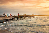 GALAPAGOS ISLANDS, ECUADOR, a group of people hanging out on the beach and watching the sunset from Fernandina Island