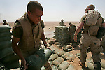 Lcpl. Levi Moore, Jr. and his comrades in Kilo Co. 3rd Battalion 1st Marines (3/1) work to rebuild and improve an outpost in the desert outside of the al-Anbar Province city of Hit, Iraq on Sun. Sept. 18, 2005. 3/1 is replacing the outgoing battered Ohio-based reserve 3rd Battalion 25th Marines.