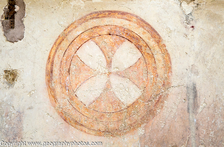 Building interior medieval circular cross symbol painted on wall of church architectural feature, Inglesham, Wiltshire, England,