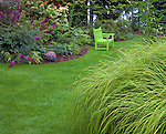 Vashon-Maury Island, WA<br /> Perennial garden featuring astillbe, Japanese forest grass and hellebores with chartreuse bench and colorful mosaic ball by tile artist, Clare Dohna