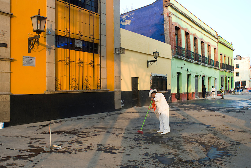 A Jarocho musician sweeps the pavement outside of La Tenampa, a popular bar in Plaza Garibaldi where Mariachis gather to be hired in Mexico City, Friday, Jan. 4, 2008