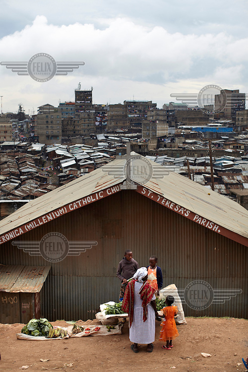 A woman buys vegetables from a stall set up near a Catholic church in the Mathare slum. This district is home to half a million people the majority of whom live in extreme poverty.