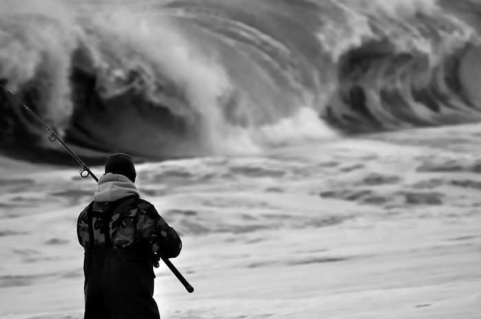 Fisherman at dawn with high waves on Fire Island