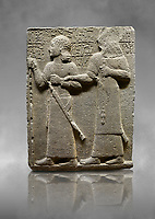 Hittite monumental relief sculpted orthostat stone panel of Royal Buttress. Basalt, Karkamıs, (Kargamıs), Carchemish (Karkemish), 900-700 B.C. Anatolian Civilisations Museum, Ankara, Turkey.<br /> <br /> King Araras holds his son Kamanis from the wrist. King carries a sceptre in his hand and a sword at his waist while the prince leans on a stick and carries a sword on his shoulder. <br /> <br /> Hieroglyphs reads; &quot;This is Kamanis and his siblings.) held his hand and despite the fact that he is a child, I located him on the temple. This is Yariris' image&quot;.  <br /> <br /> Against a grey art background.