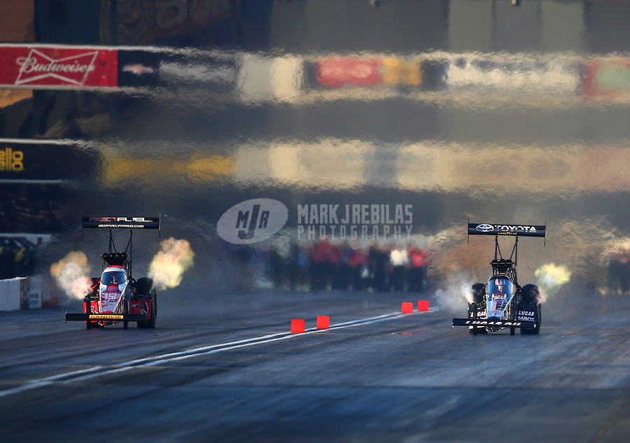 Feb 13, 2016; Pomona, CA, USA; NHRA top fuel driver Shawn Langdon (left) races alongside Morgan Lucas during qualifying for the Winternationals at Auto Club Raceway at Pomona. Mandatory Credit: Mark J. Rebilas-USA TODAY Sports