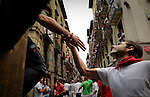 A runner greets a shepherd of Encierro before the fourth run of the bulls of the San Fermin festival, on July 10, 2012, in the Northern Spanish city of Pamplona. The festival is a symbol of Spanish culture that attracts thousands of tourists to watch the bull runs despite heavy condemnation from animal rights groups. (c) Pedro ARMESTRE