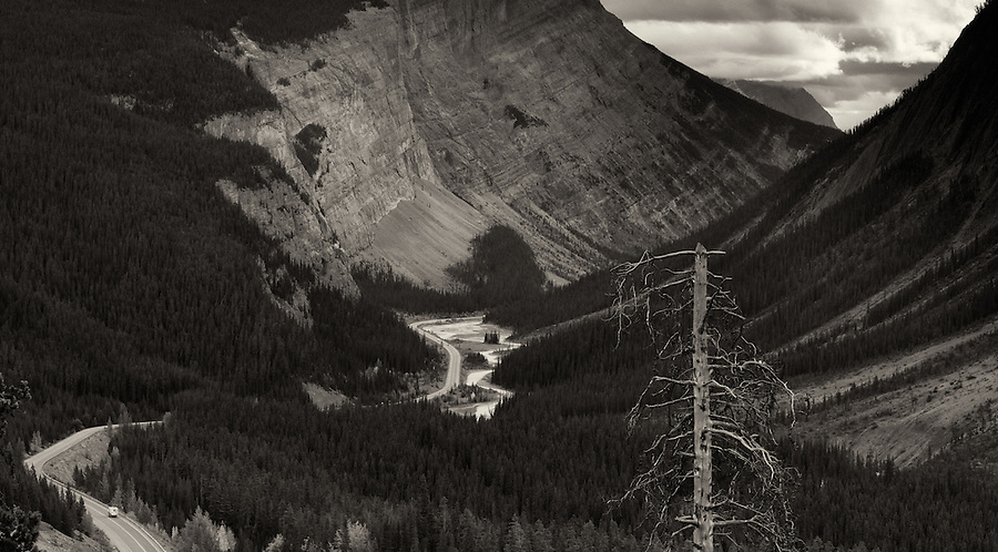 Highway 93, also known as the Icefields Parkway, disappears into the Rocky Mountains underneath a stormy sky.