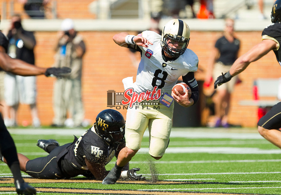 WINSTON SALEM, NC - SEPTEMBER 22: Army Black Knights quarterback Trent Steelman (8) stumbles forward after having been tripped up by Kevin Johnson (9) of the Wake Forest Demon Deacons at BB&T Field on September 22, 2012 in Winston Salem, North Carolina.  The Demon Deacons defeated the Black Knights 49-37.  (Photo by Brian Westerholt/Sports On Film)