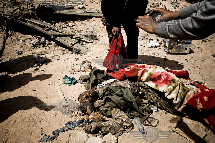 A dead Gaddafi loyalist soldier lies on the side of the road on the eastern outskirts of Ajdabiya after a Nato air strike. A rebel takes a photograph of him as he is covered up. On 17 February 2011 Libya saw the beginnings of a revolution against the 41 year regime of Col Muammar Gaddafi.