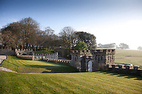 A castellated curtain wall borders the east side of Prideaux Place. A gate in the stone wall leads to the deer park in the distance