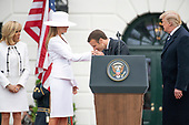 President Emmanuel Macron of France kisses the hand of first lady Melania Trump during an arrival ceremony on the South Lawn of the White House in Washington, DC on Tuesday, April 24, 2018. United States President Donald J. Trump, left, and Brigitte Macron, left, look on.<br /> Credit: Ron Sachs / CNP
