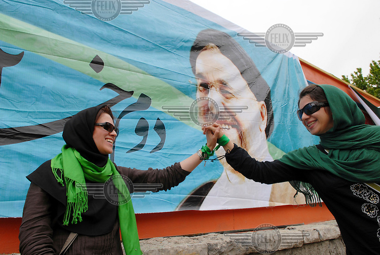 Female supporters of former prime minister Mir-Hossein Mousavi at a rally at Heravi stadium before the 2009 presidential election. Behind them is a billboard featuring former president Mohammad Khatami, a supporter of Mousavi's candidature.
