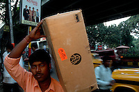 An Indian man carries a curtain with a logo of Cisco in Kolkata, India  6/13/2007  Arindam Mukherjee