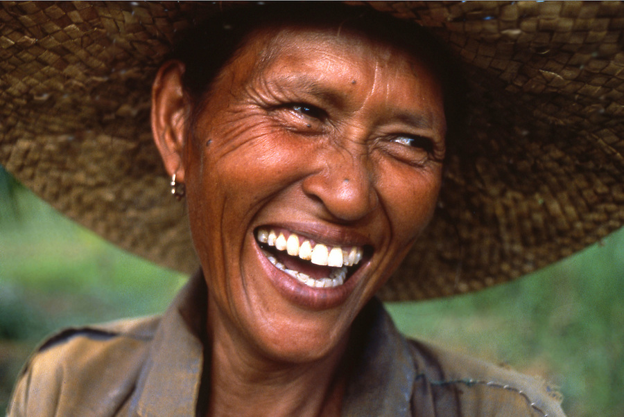 A farmer woman breaks a wide smile in the Philippines.