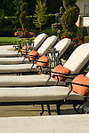 a row of high-end poolside patio lounges with colorful orange red accent cushions sit in the late afternoon summer sun backed by a vibrant summer garden of colorful annuals and sculpted evergreen topiary