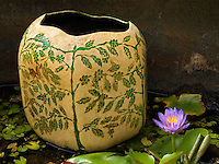 Hawaiian gourd decorated in ancient Ni'ihau style, floating in lily pond