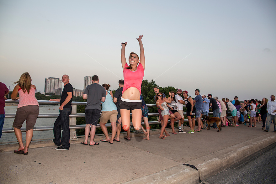 Cheerful attractive Austin woman leaps for joy on the Congress Ave. Bat Bridge in downtown Austin, Texas.
