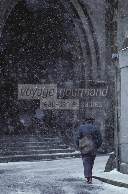 Europe/France/Auvergne/15/Cantal/Salers: Le porche de l'église XII ème siècle et le facteur qui  hate le pas parmi les flocons de neige