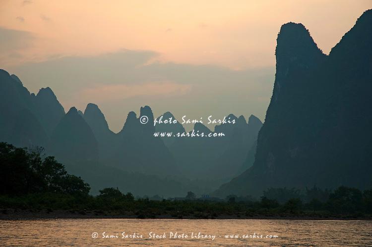 Looking across the Li Jiang River at the limestone mountain peaks between Xinping and Yangshuo, Guangxi, China.