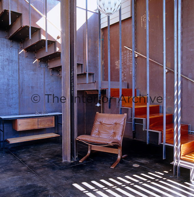 A retro chair and desk at the bottom of the metal cantilevered staircase in the entrance hall