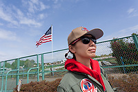 Military aircraft enthusiast, Rina Omatsu watches the sky in front of an American flag in a park near Naval Air facility, Atsugi airbase. Yamato, Kanagawa, Japan. Monday April 29th 2019
