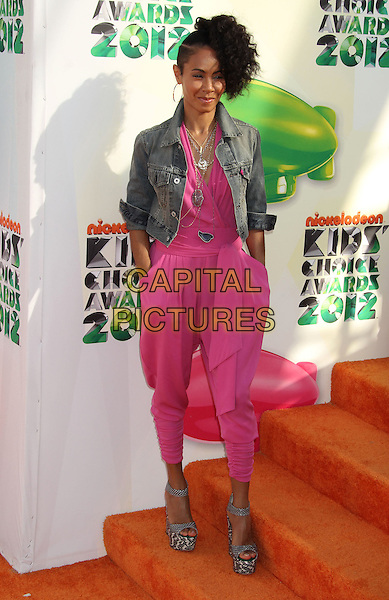 Jada Pinkett Smith.2012 Nickelodeon Kids' Choice Awards held at the Galen Center, Los Angeles, California, USA..March 31st, 2012.full length shaved head hair mohawk denim jacket pink catsuit jumpsuit necklaces hands in pockets platform sandals .CAP/ADM/RE.©Russ Elliot/AdMedia/Capital Pictures.