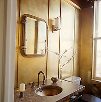 In this bathroom glamorous gold leaf covers the panelled walls and a mirror in the shape of a steamer window gives the feeling of an old-fashioned ocean liner
