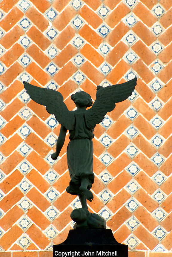 Angel statue with Talavera tile facade in background, city of Puebla, Mexico. The historic center of Puebla is a UNESCO World Heritage Site.
