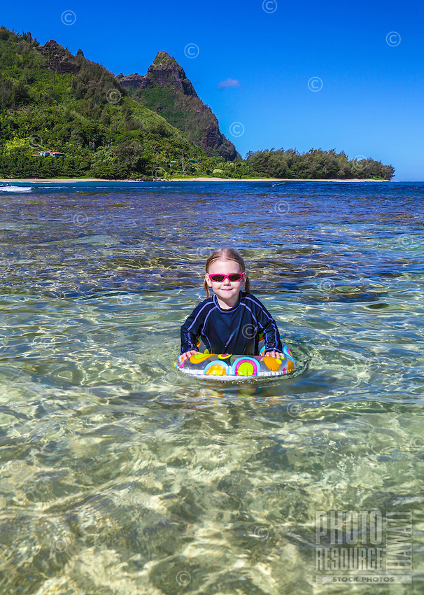 A young girl enjoys a day at the beach at Ha'ena State Park, with Mt. Makana (also called Bali Hai) in the distance, Kaua'i.