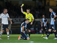 Referee Gavin Ward Issues Jamie O'Hara (left) of Fulham a yellow for a foul on floored Garry Thompson of Wycombe Wanderers during the Capital One Cup match between Wycombe Wanderers and Fulham at Adams Park, High Wycombe, England on 11 August 2015. Photo by Andy Rowland.