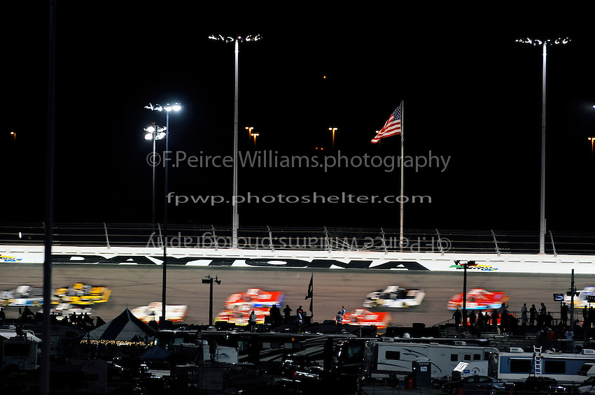 """Truck speed past the """"Daytona"""" signage in turn 3."""