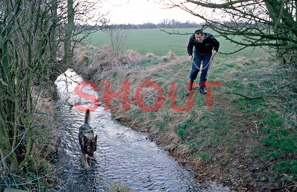 Police Dog Handler with his Alsatian Dog. The dog has been given an article of clothing to smell and is setting off to trace the person. This image may only be used to portray the subject in a positive manner..©shoutpictures.com..john@shoutpictures.com