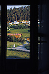 View through window of country lane, farm buildings and houses against forest background.Imst district,Tyrol, Austria.