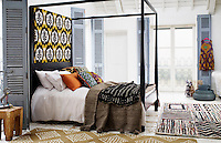 A black lacquer four-poster bed is dressed with ethnic fabrics and the distressed wooden floor of the bedroom is covered with ethnic rugs