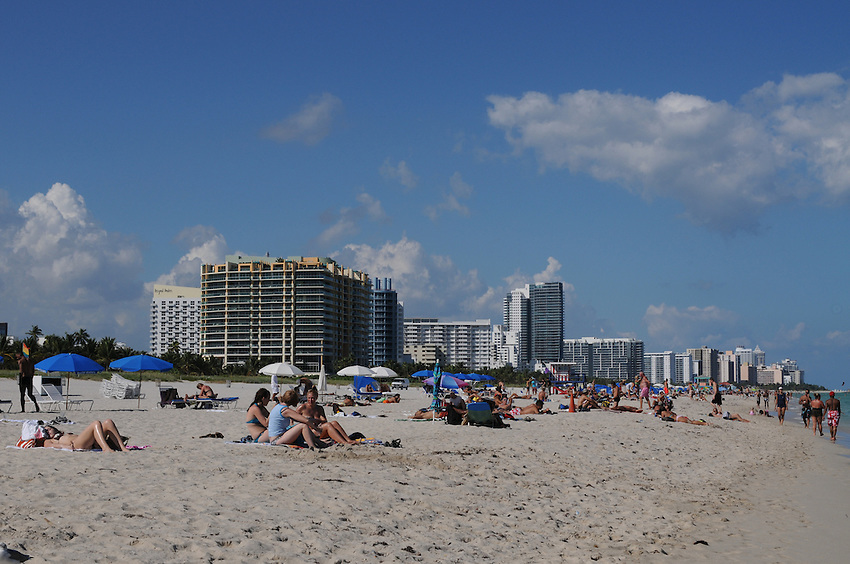 People enyoying the sun sand and warm ocean waters of beautiful Miami Beach Florida.