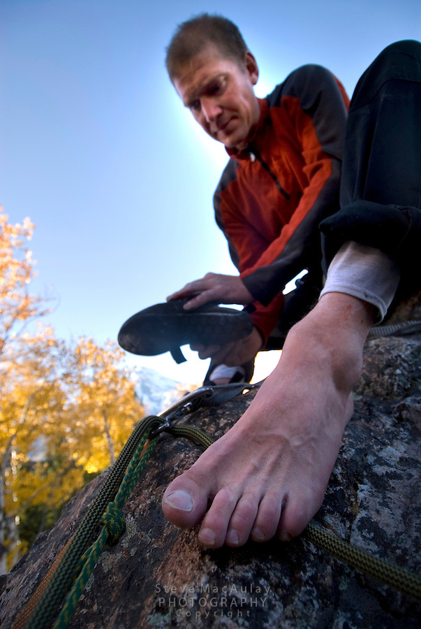 Close-up of foot of male rock climber sitting on boulder as he puts on his climbing shoes, Fall, Grand Teton National Park, Wyoming