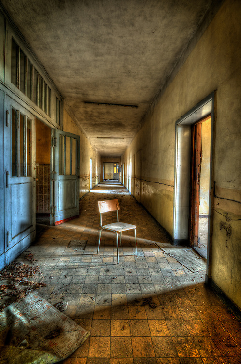 Interior of decaying old tanks barracks somewhere near Berlin with chair in corridor and sunlight
