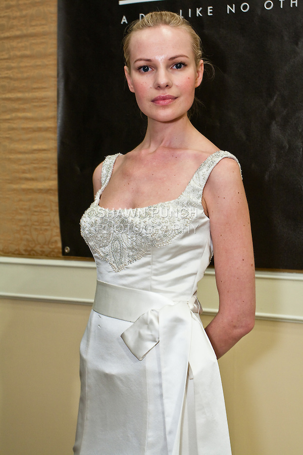 Model poses in an Anne Gown - Duchesse Satin, slim A-line with full hem, embellished tank style bodice with natural waist and embellished sash, by Elizabeth Mary Blankenship, for the Ann Frances Fall 2010 collection, presented at the Wedding Channel Couture Show, during New York  Bridal Fashion Week Fall 2010.