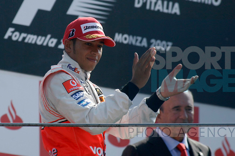 Lewis Hamilton applauds the fans he waits on the winners podium