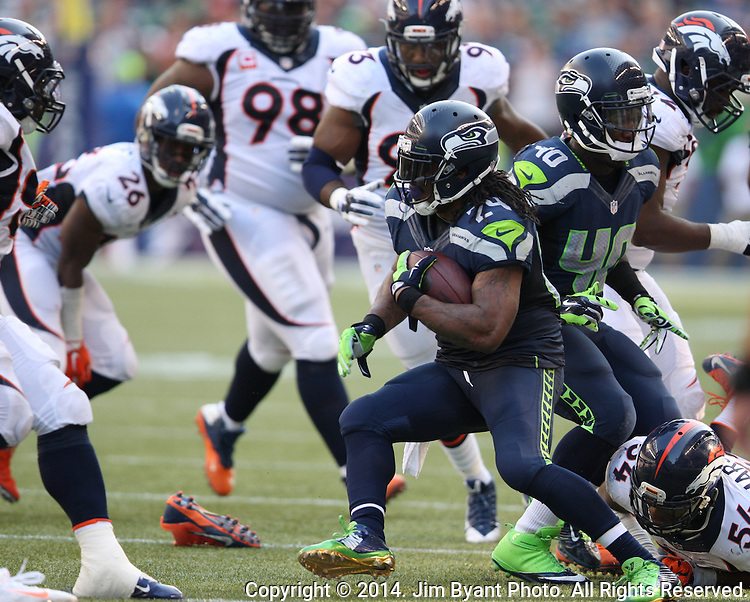 Seattle Seahawks running back Marshawn Lynch (24) looks for running room against  Denver Broncos safety Rahim Moore (26) after breaking a tackle by linebacker Brandon marshall (54)in the fourth quarter at CenturyLink Field in Seattle, Washington on September 21, 2014.   Lynch ran for 88 yards and scored two touchdowns in the Seahawks 26-20 overtime win over the Broncos.   ©2014. Jim Bryant Photo. All rights Reserved.