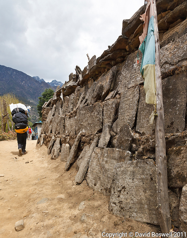 A sherpa carries bags next to mani stones on the trail to Everest Base Camp in Nepal.
