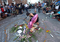 A woman lays down flowers during a large vigil for Heather Heyer Sunday night at 4th Street SE and Water Street in Charlottesville, Va. Heyer was killed and 19 others injured when a car intentionally ran through a crowd of counter protestors after the Unite The Right rally. Photo/Andrew Shurtleff/The Daily Progress