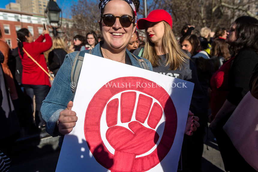 New York, USA 8 March 2017 - Women marked International Women's Day - A Day Without a Woman, with a rally in Washington Square Park followed by a march. Many women wore red and took the day off as a general strike. Woman with a sign showing the symbol for Womann Power in red. ©Stacy Walsh Rosenstock/Alamy Live News